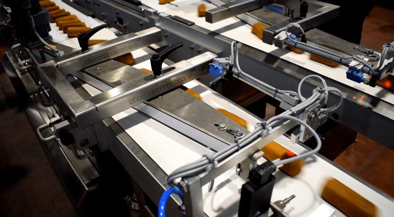 El dispositivo de giro de productos se utiliza para girar los productos 90 grados desde una posición de entrada de borde ancho a una orientación de entrada de borde estrecho.