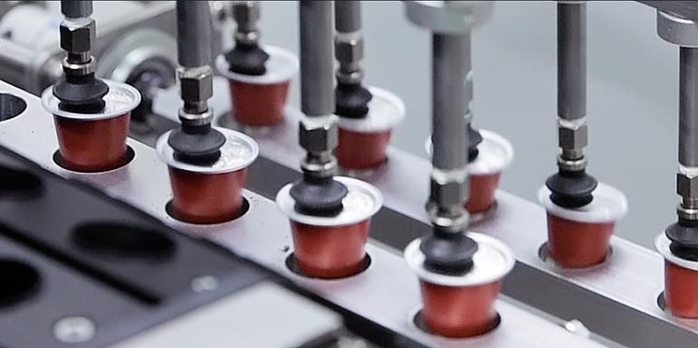 Sistema automatizado de extracción de las cápsulas de aluminio para café, té o solubles, llenas y selladas.