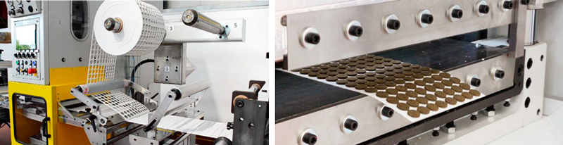 A la izquierda podemos ver la lámina de soporte y la bobina con el laminado sobrante. A la derecha las tapetas adhesivas troqueladas a punto de ser cortadas por la guillotina